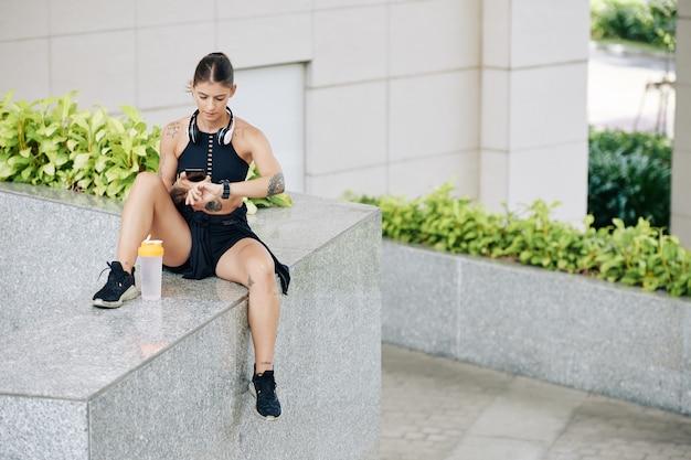 Fit serieuze jonge vrouw controlerende activiteitstracker na het joggen buiten in de ochtend