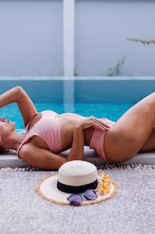 Fit slanke vrouw in bikini op de rand van het zwembad genieten van vakantie