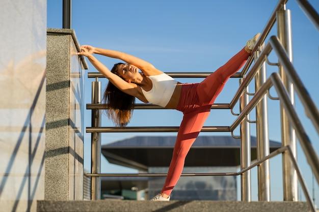 Fit sportieve vrouw buigen en strekken op trapleuning buitenshuis