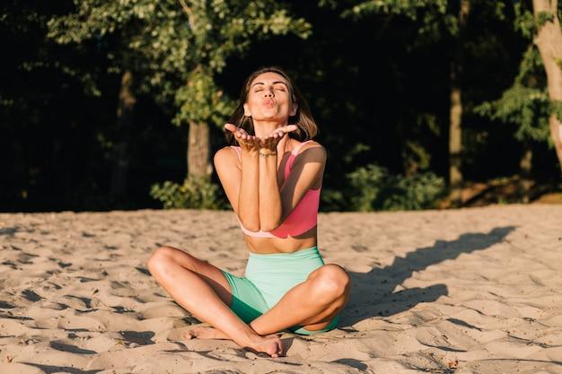 Fit sportieve vrouw in perfecte vorm bij zonsondergang op het strand in yoga pose kalm