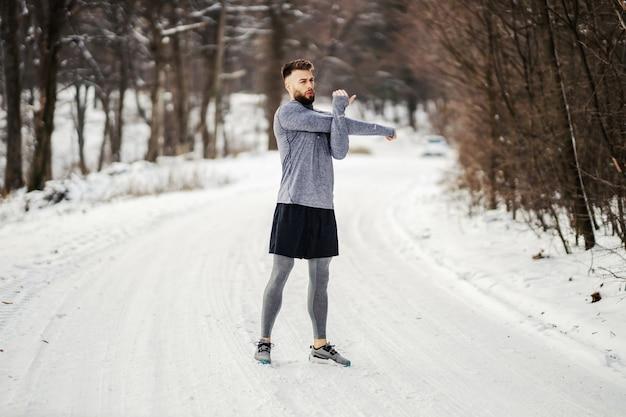 Fit sportman die rek- en opwarmingsoefeningen doet terwijl hij in de winter op een besneeuwd pad in het bos staat. gezond leven, winterfitness, koud weer