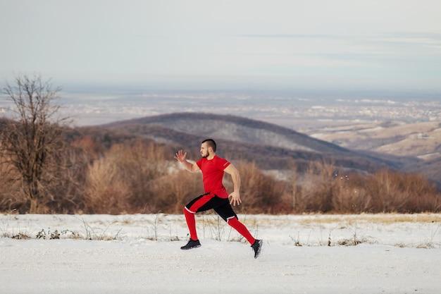 Fit sportman sprinten op sneeuw in de natuur in de winter. winterfitness, gezond leven