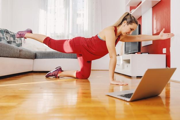 Fit sportvrouw die thuis op de grond knielt en fitnessoefeningen doet terwijl ze online les volgt.