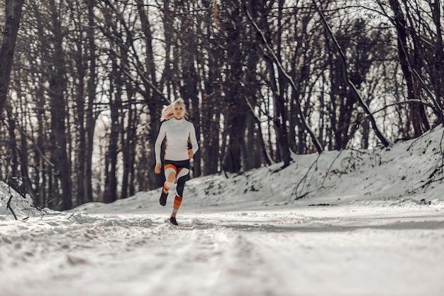 Fit sportvrouw draait op besneeuwde pad in de natuur in de winter. sporten, cardio-oefeningen, winterfitness