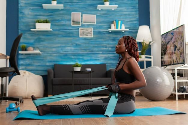Fit sterke afro vrouw training thuis woonkamer met behulp van weerstandsband zittend op fitness mat trekken...