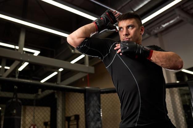 Fit sterke man bokser in handschoenen staan in de strijd pose tijdens de training. concept van sterkte en motivatie. kickboksen, mma, sportconcept