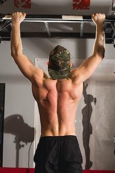 Fit tenen om man pull-ups bars training oefening op sportschool te versperren