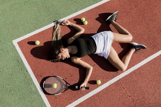 Fit tennisspeler op de grond