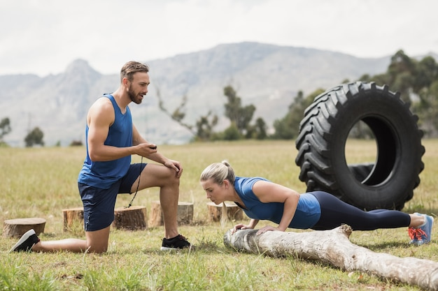 Fit uitvoeren van push-up-oefening terwijl de man de tijd meet in het bootcamp