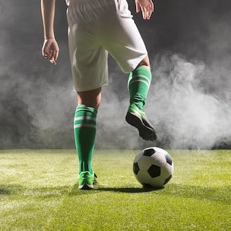 Fit voetballer in sportkleding met bal