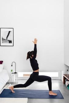 Fit vrouw beoefenen warrior i pose tijdens een yoga training thuis