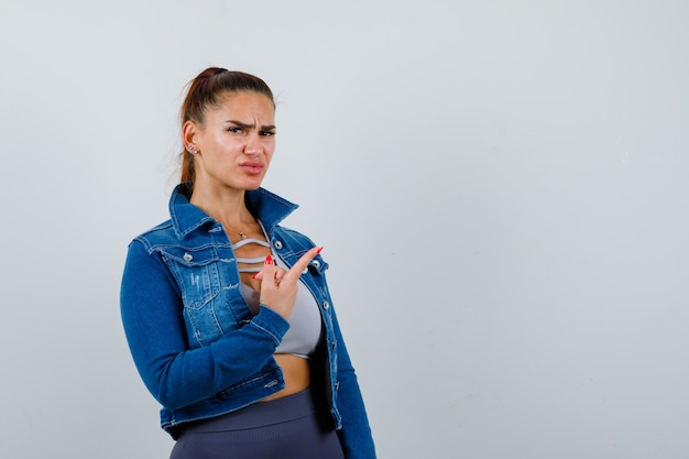 Fit vrouw die met wijsvinger naar rechts wijst, kusjes stuurt in crop top, spijkerjasje, legging en er gehaast uitziet. vooraanzicht.