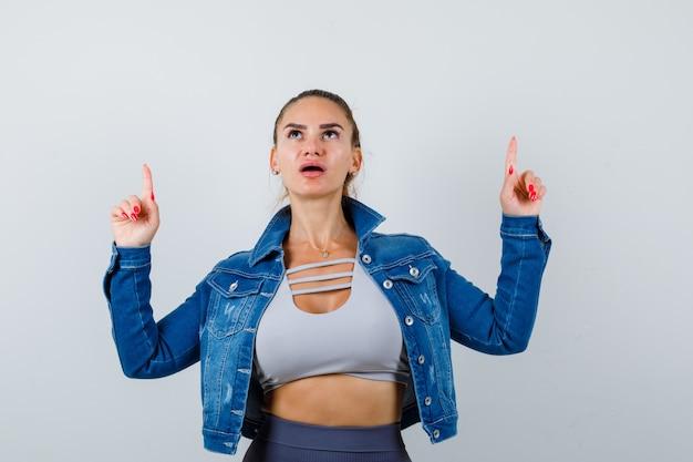 Fit vrouw die met wijsvingers omhoog wijst in crop top, spijkerjasje, legging en verbaasd kijkt. vooraanzicht.