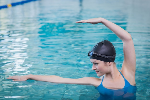 Fit vrouw die zich uitstrekt in het water bij het zwembad