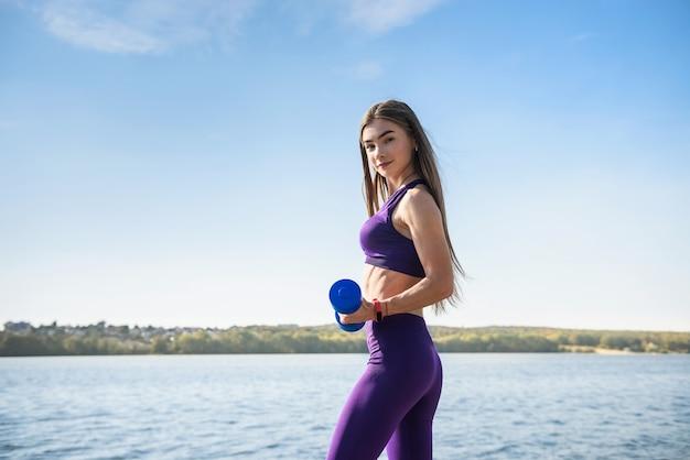 Fit vrouw doen oefening met halters in haar handen in de natuur, vlakbij het meer