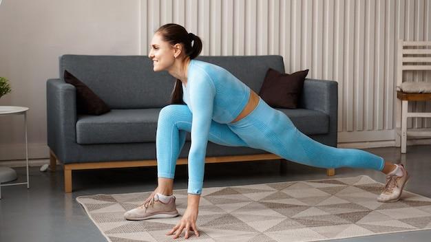 Fit vrouw doet front forward een been stap lunge oefeningen training thuis.