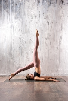 Fit vrouw doet salamba sarvangasana yoga pose