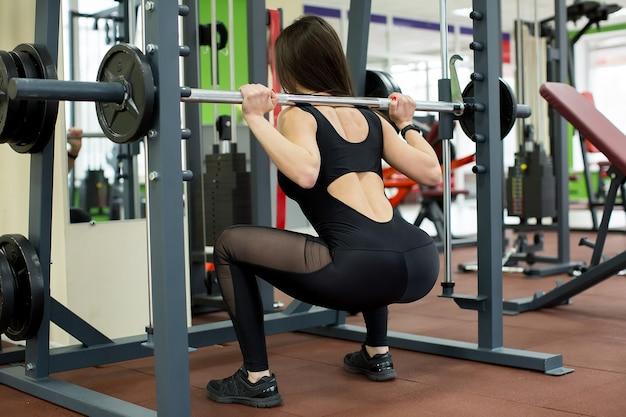 Fit vrouw doet squats met een barbell in smith machine