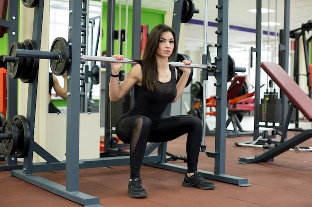 Fit vrouw doet squats met een halter in de smith-machine