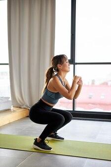 Fit vrouw doet squats thuis op de mat, in lichte kamer. ze sport, wil gespierde benen