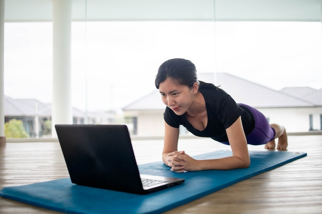 Fit vrouw doet yoga en kijken naar online tutorials op notebook
