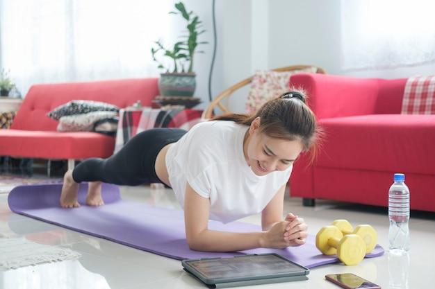 Fit vrouw doet yoga plank en kijken naar online tutorials, training in de woonkamer. blijf thuis in de levensstijl.