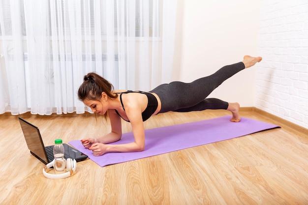 Fit vrouw doet yoga plank en kijkt naar online tutorials op laptop