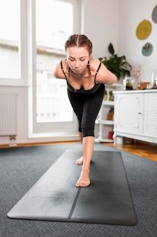 Fit vrouw doet yoga thuis vooraanzicht