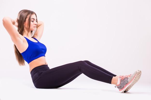 Fit vrouw haar been strekken om op te warmen geïsoleerd op witte achtergrond