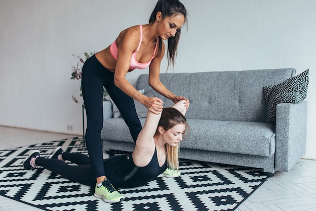 Fit vrouw helpen vriend in rug uitrekkende training thuis.