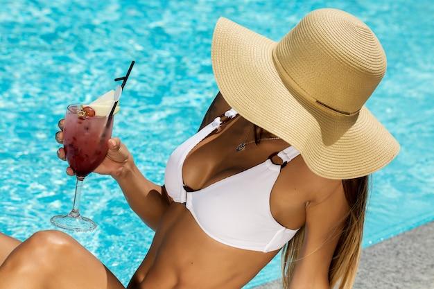 Fit vrouw in bikini en cocktail op het zwembad
