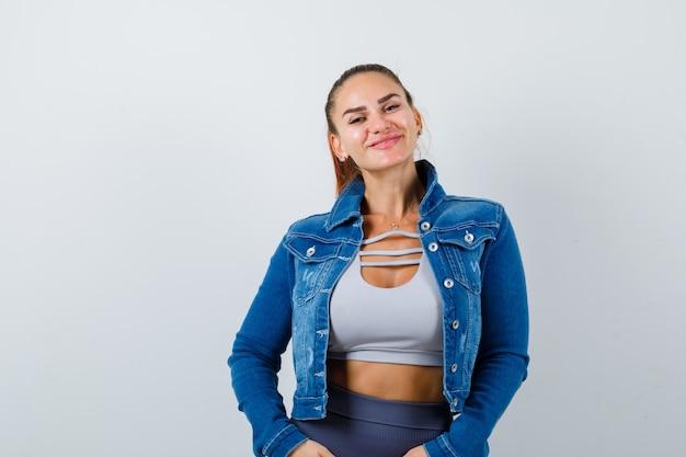 Fit vrouw in crop top, spijkerjack, legging glimlachend terwijl ze voor de camera poseert en er vrolijk uitziet, vooraanzicht.