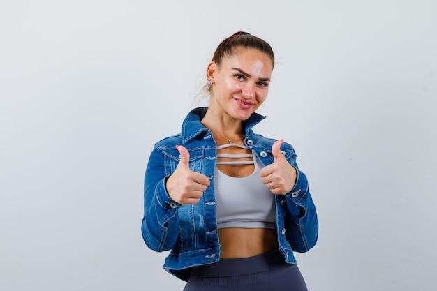 Fit vrouw in crop top, spijkerjasje, legging met dubbele duimen omhoog en vrolijk, vooraanzicht.