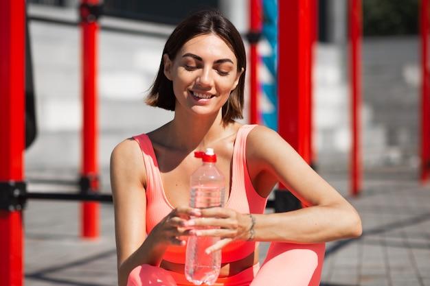 Fit vrouw in roze sportkleding buiten passen met fles water