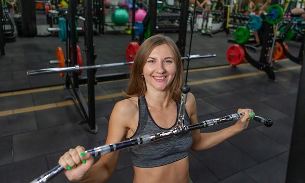 Fit vrouw in sportkleding oefening met oefening gewicht machine in sportschool. aantrekkelijk meisje opleiding. fitness, sportconcept