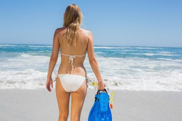 Fit vrouw in witte bikini met snorkeluitrusting op het strand