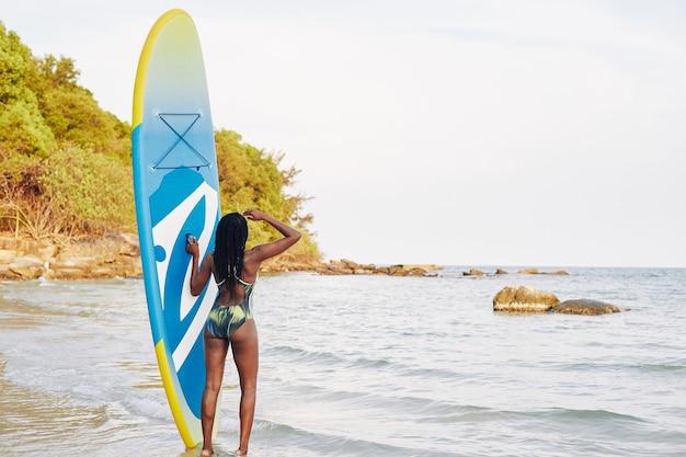Fit vrouw kijken naar zee golven