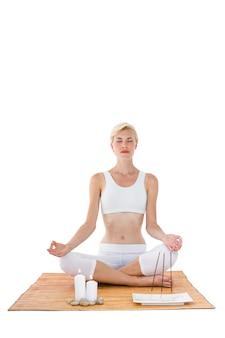 Fit vrouw mediteren op bamboe mat