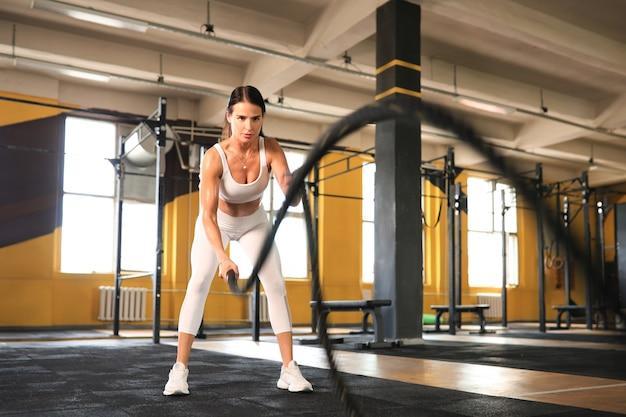 Fit vrouw met behulp van battle ropes tijdens krachttraining in de sportschool.