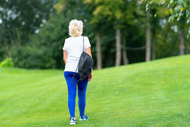 Fit vrouw met een sporttas over haar schouder weglopen over het groene gras in een park naar verre bomen