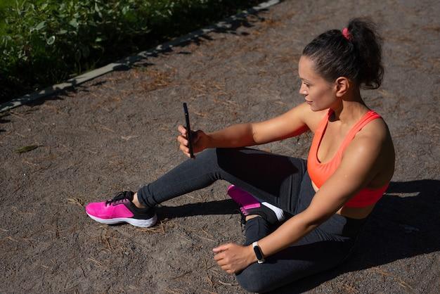 Fit vrouw met fitness tracker op pols en smartphone cheking informatie van training. gebruik van elektronische gadgets en moderne it-technologieën in een gezond leven