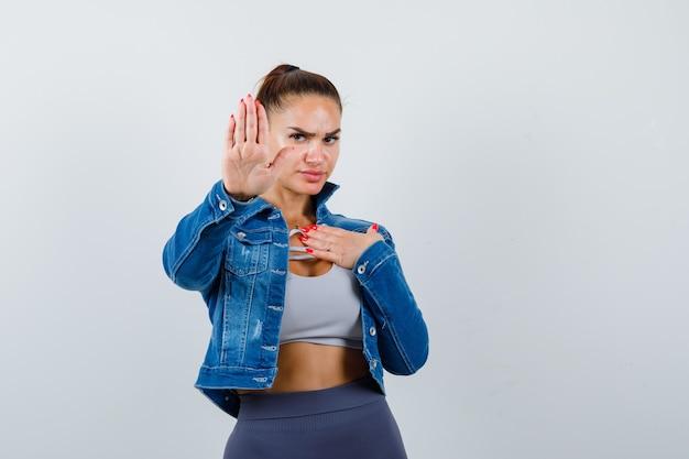 Fit vrouw met stopbord, met hand over borst in crop top, spijkerjasje, legging en zelfverzekerd, vooraanzicht.