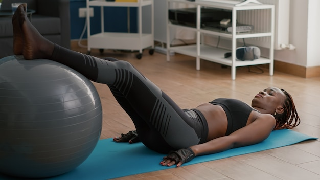 Fit vrouw met zwarte huid die buikspieroefeningen doet met behulp van fitball buigende buikspieren