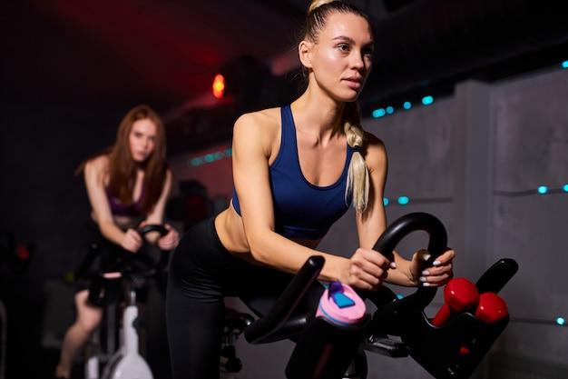Fit vrouw op de sportschool uit te oefenen op een hometrainer in de sportschool. cardio-oefeningen op de fiets, in sportieve kleding, geconcentreerd op training