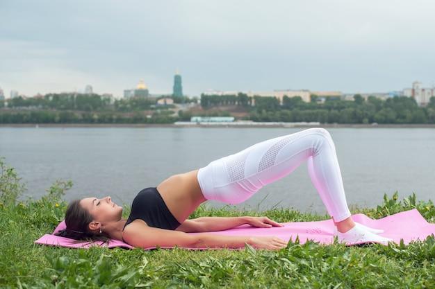 Fit vrouw praktijken yoga asana setu bandhasana brug pose
