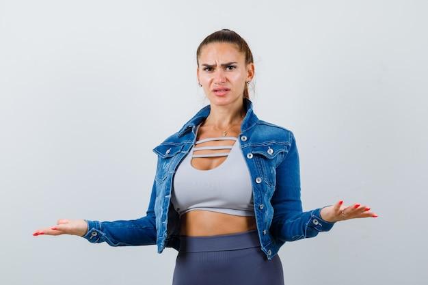Fit vrouw spreidt handpalmen op een onwetende manier in crop top, spijkerjasje, legging en ziet er verward uit. vooraanzicht.