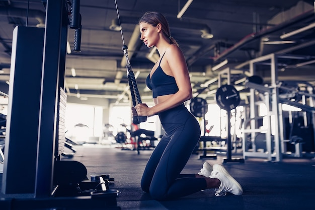 Fit vrouw training triceps tillen gewichten in de sportschool. atletische sexy vrouw die oefening doet die machine in gymnastiek gebruikt.