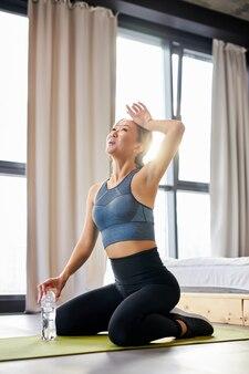 Fit vrouw zit zweet van haar gezicht te vegen, rust, moe na zware oefeningen, thuis trainen