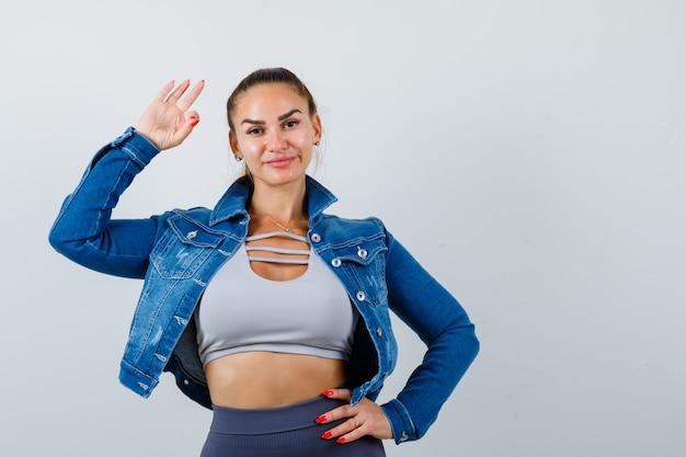 Fit vrouw zwaaiend met de hand om te begroeten, met de hand op de heup in crop top, spijkerjasje, legging en vrolijk kijkend. vooraanzicht.