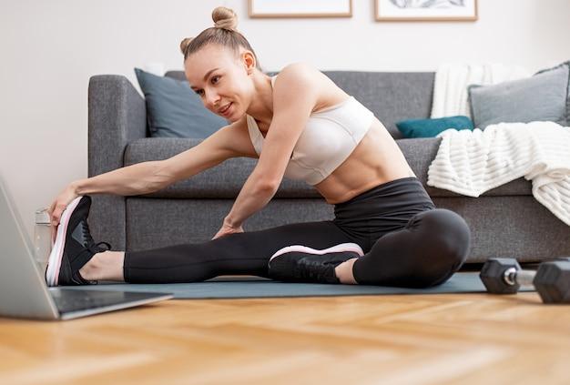 Fit vrouwelijke atleet buigen aan het been en lichaam uitrekken in de buurt van laptop tijdens online training in de buurt van sofa thuis